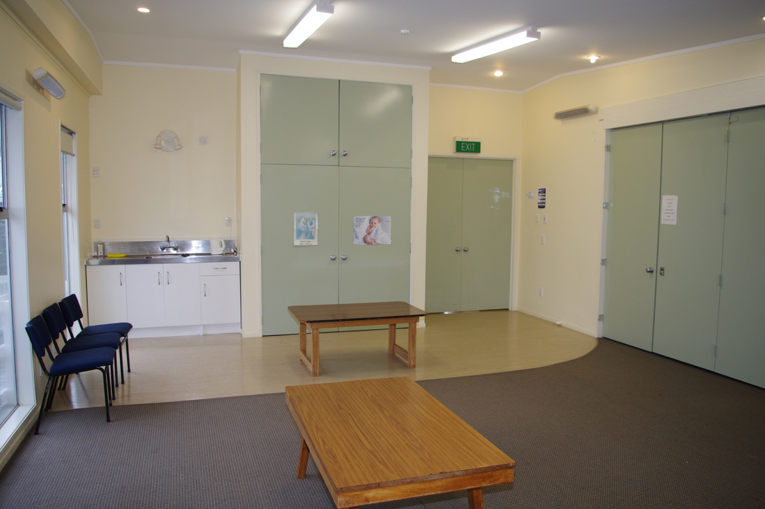 Picture of the North Room of the Emmaus Centre at St Chrsitopher's Anglican Church in Tawa. A small kitchen bench and sink can be seen at the eastern end of the room, surrounded by hard flooring. The western part of the room is carpeted and large folding doors on the south side open into the adjacent Middle Room